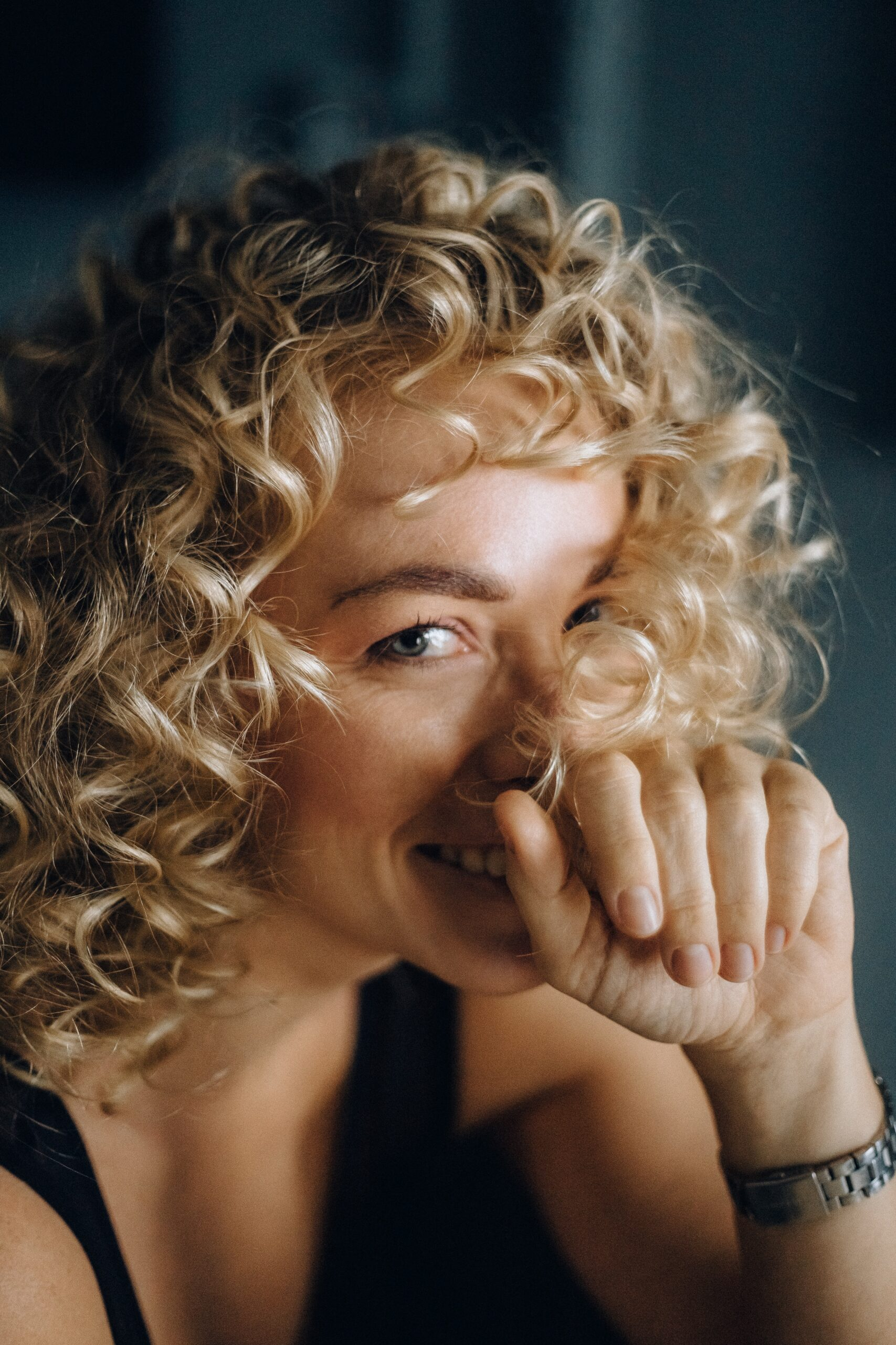 Blonde haired woman smiling with her hand on her face