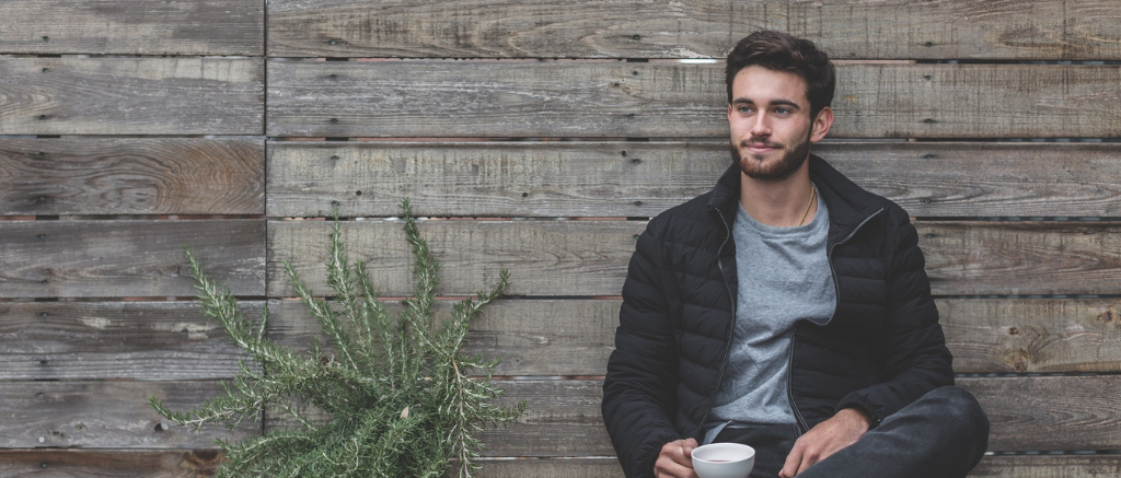 Young man sitting alongside wall holding a cup of coffee